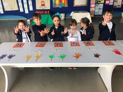 Crianças usam mãos para aprender sobre quantidade
